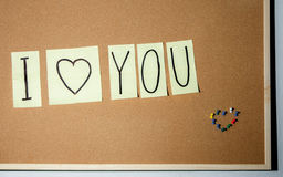 Paper note written with I LOVE YOU inscription on cork board. Stock Photos