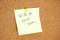 Paper note written with WE`LL BE BACK SOON inscription on cork board. Stock Image