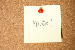 Paper note written with NOTE inscription on cork board. Royalty Free Stock Photo