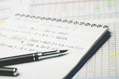 Paper notebook with accounting calculations and pen on the background of the table royalty free stock photos