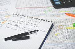 Paper notebook with accounting calculations and pen on the background of a table with numbers stock images