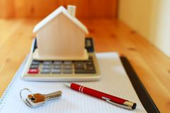 Paper notebook with calculator, house model, keys and pen on wooden table. stock photography