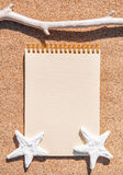 Paper notebook, dry branch and seashells on the sand Royalty Free Stock Images