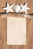 Paper notebook, dry branch and seashells on the sand Royalty Free Stock Image