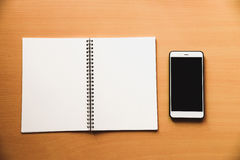 Paper notebook for memo message with smart phone on wooden desk.  royalty free stock image