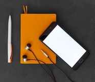 Paper notebook, mobile phone, pen and headphones on dark background top view. Orange paper notebook, mobile phone, pen and headphones on dark background top view stock images