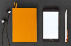 Paper notebook, mobile phone, pen and headphones on dark background top view. Orange paper notebook, mobile phone, pen and headphones on dark background top view stock image