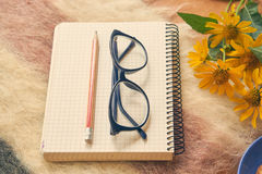 Paper notebook with pen and glasses on woolen plaid Royalty Free Stock Photography