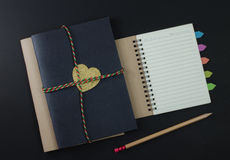 paper notebook pencils on black background Royalty Free Stock Photos