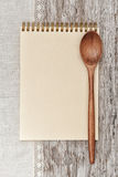 Paper notebook, wooden spoon and linen fabric on the old wood. En background Stock Images