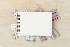 Paper notepad mock up in frame of various blisters with multi-colored tablets and capsules on wooden table. Doctor desk. Background, horizontal medical concept stock image