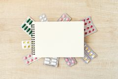 Paper notepad mock up in frame of various blisters with multi-colored tablets and capsules on wooden table. Doctor desk. Background, horizontal medical concept royalty free stock image