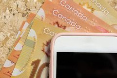 Paper notes from Canada. Dollar. Blank cel phone screen and bills on marble. Paper notes from Canada. Dollar. Canadian cash. Blank cel phone screen and bills on stock images
