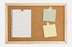 Paper notes on cork. Cork Pin Board  with a sheet of paper, post it notes, and thumbtacks Royalty Free Stock Photos