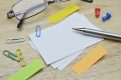 Paper notes, glasses; pencil, clip, mouse and keyboard on table Stock Images