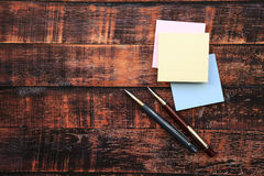 Paper notes with pens on wooden background Royalty Free Stock Photo