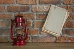 Paper and old kerosene lantern Stock Photography