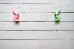 Paper origami handmade pink, green bunnies on white planks barn wood boards background Royalty Free Stock Photography