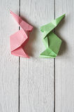 Paper origami handmade pink, green bunnies on white planks barn wood boards background Stock Photo