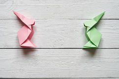 Paper origami handmade pink, green bunnies on white planks barn wood boards background Royalty Free Stock Photo