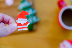 Paper origami Santa Claus on hand. With blurred background Royalty Free Stock Photos