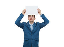 Paper over head. Young Businessman looking up and holding a white paper over head Royalty Free Stock Photo