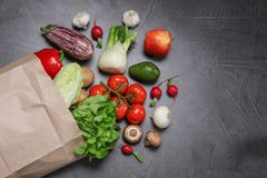 Paper package with fresh vegetables and fruits on dark background, flat lay. Space for text stock image