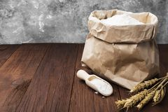 Paper package of wheat flour on a wooden background.  Royalty Free Stock Images