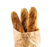 Paper packet with home baked baguettes on white. Royalty Free Stock Photo