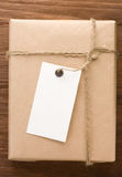 Paper parcel wrapped tied with price tag on wood royalty free stock image