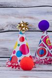 Paper party hats and other decorations. Kids Birthday party supplies on wooden background royalty free stock photography