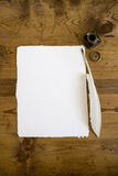 Paper and pen. A sheet of white hand made paper with quill pen and ink on an antique desktop. Includes copy space Royalty Free Stock Images