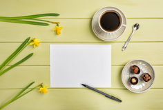 Paper, a pen, cup of black coffee and flowers. Flat lay. Stock Image