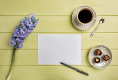 Paper, a pen, cup of black coffee and flowers. Flat lay. Royalty Free Stock Photography