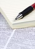Paper and Pen on Dictionary. A notepad and pen lay on top of a dictionary...finding the right word Royalty Free Stock Images