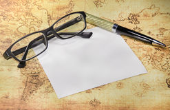 Paper,pen and eyeglasses on a old world map Stock Image