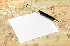 Paper and pen on a old world map Stock Photo