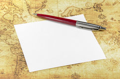 Paper and pen on a old world map Stock Image