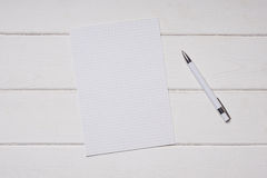 Paper and pen on white wooden desk Stock Photography
