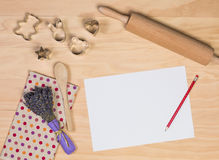 Paper, pencil and some kitchen utensils. On wooden background Royalty Free Stock Photo