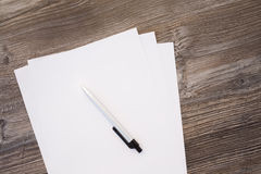 Paper and pencil on wooden table Stock Photos