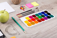 Paper, pencils, brush, green apple on wooden table Royalty Free Stock Images