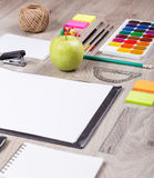 Paper, pencils, brush, green apple on wooden table Royalty Free Stock Photography