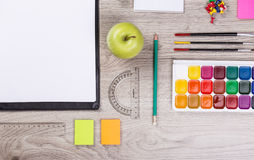 Paper, pencils, brush, green apple on wooden table Stock Image