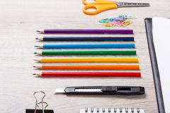 Paper, pencils, brush, green apple on wooden table Stock Photography