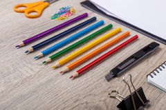 Paper, pencils, brush, green apple on wooden table Royalty Free Stock Image