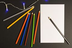 Paper with pencils on a dark background royalty free stock photo