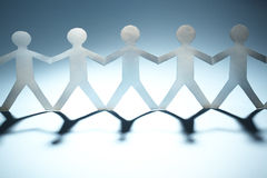 Paper people. Chain of paper people on blue Royalty Free Stock Photos