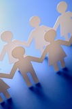 Paper people. Cutout paper people on a blue background Royalty Free Stock Photography