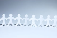 Paper people chain. Forming heart between figures Royalty Free Stock Photo